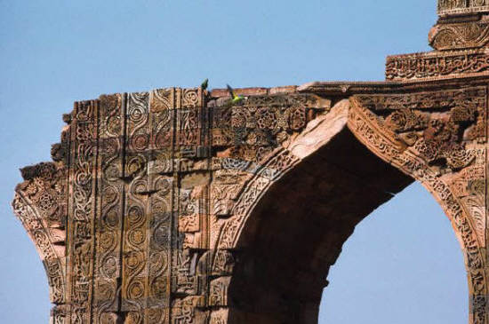 Islamic script and arabesques decorate the ruins of an ogee arch at Qutb mosque
