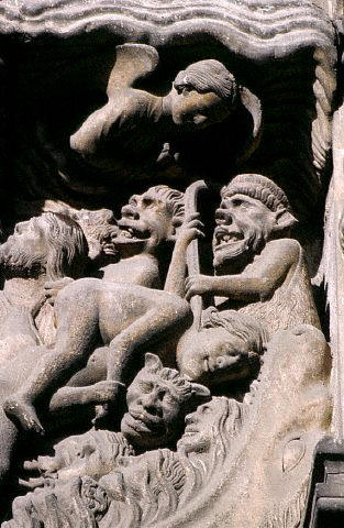 A sculpture including statues of goblins decorates the south porch of The Cathedral of Notre Dame,  France.