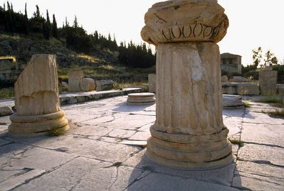 Fragmentary columns on a worn stone pavement flank the propylea, or entrance to the sacred area, at the ruins of Eleusis