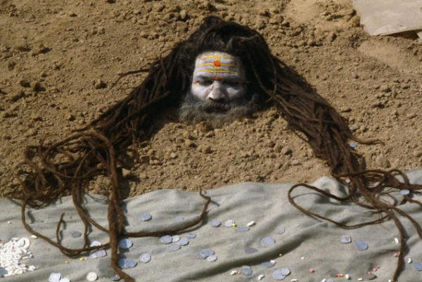 A sadhu buries his body in sand during a solar eclipse ceremony in Kurukhshtra
